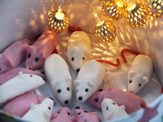 Tin of sugar mice, lit by elaborate christmas fairylights.