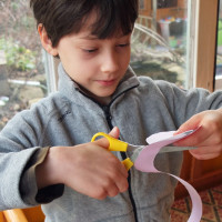 Young boy working on a paper rose.