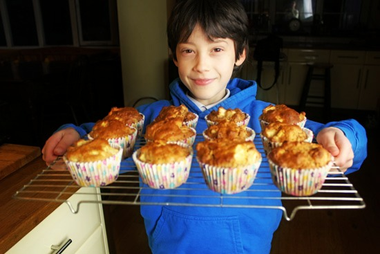 Young boy proudly holding the muffins he has made.
