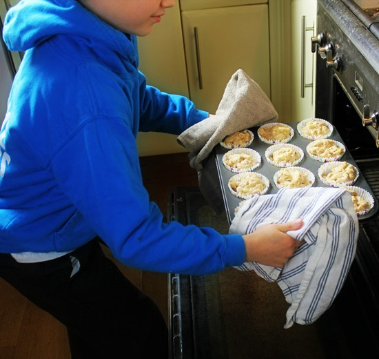 Carefully putting the muffins into the oven.