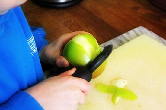 Peeling a green apple.