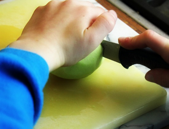 Slicing a peeled apple with a knife.