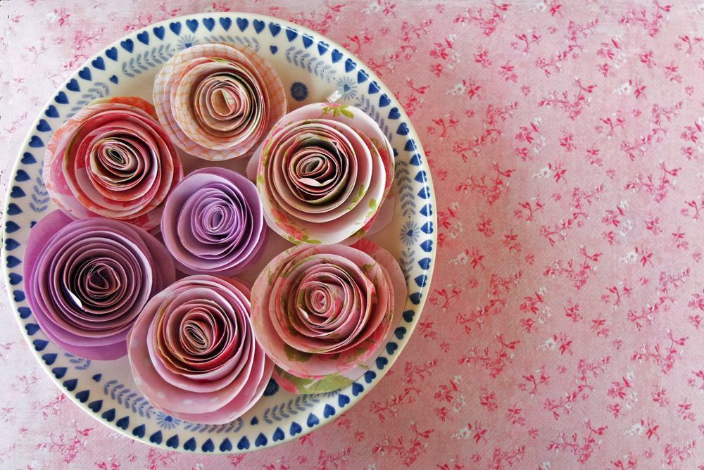 Bowlful of multicoloured paper roses on a flowery backdrop.