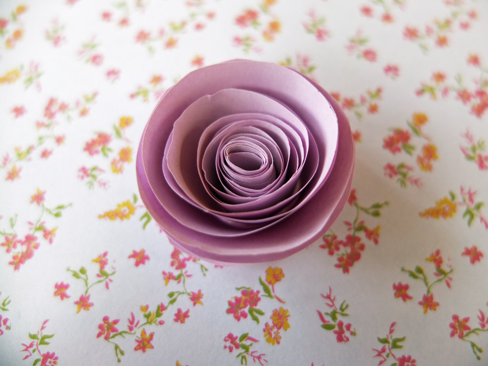 Lilac paper rose on a flowery background.