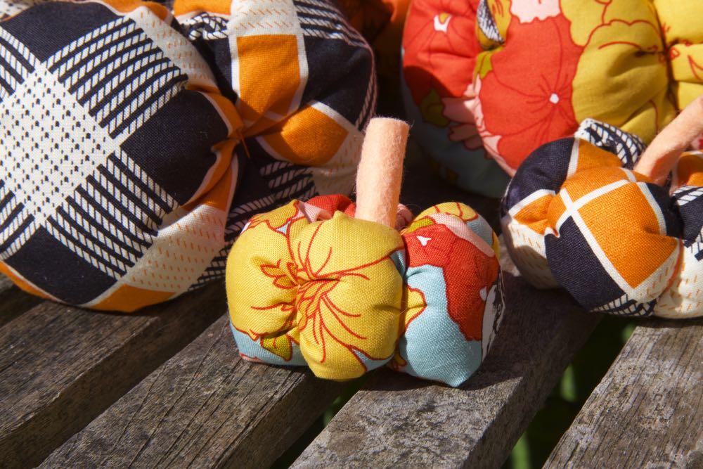 Fabric munchkin pumpkins surrounded by larger pumpkins.