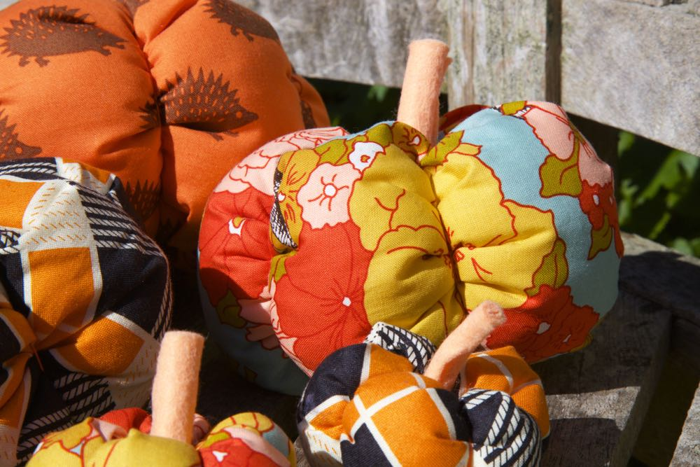 A pile of brightly coloured fabric pumpkins.