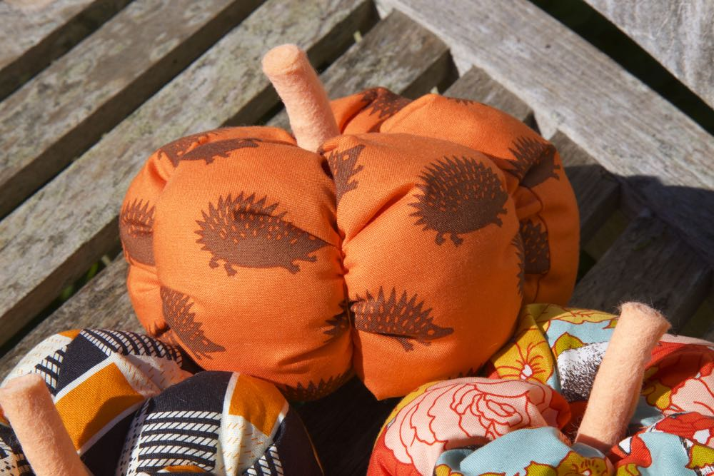 Fabric pumpkins with rolled felt stalks outside on a bench.