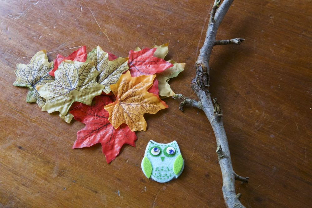 Paper leaves, a stick and a small felt owl.