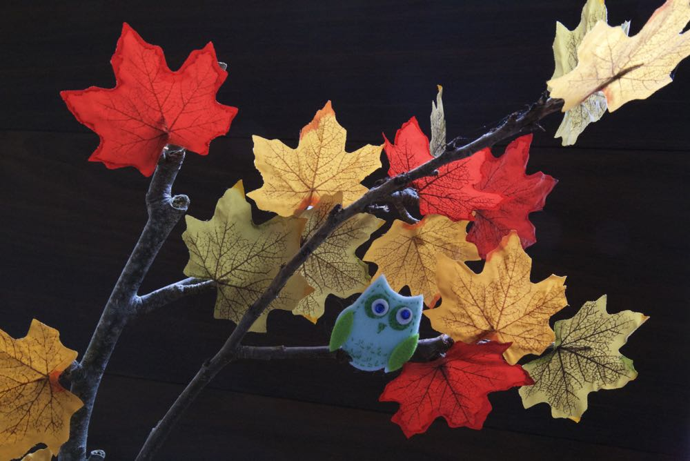Autumn tree decoration with paper leaves and a small felt owl.