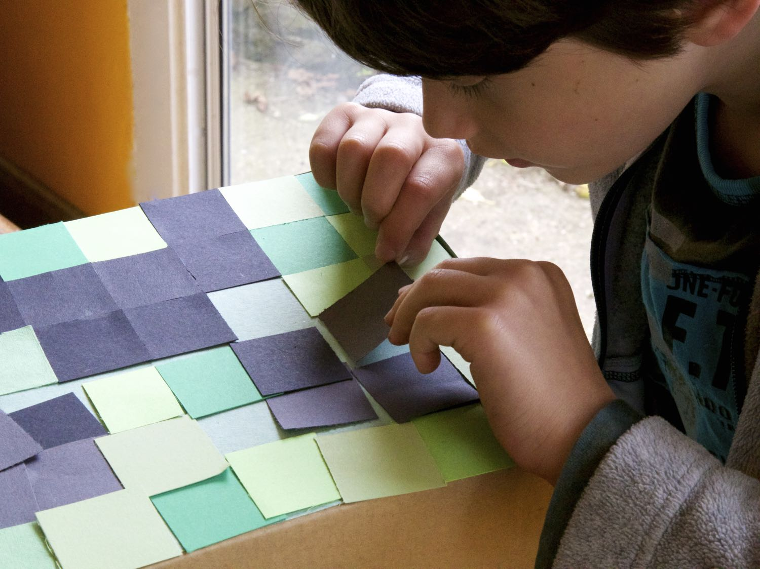 Arranging the paper squares into a creeper face.