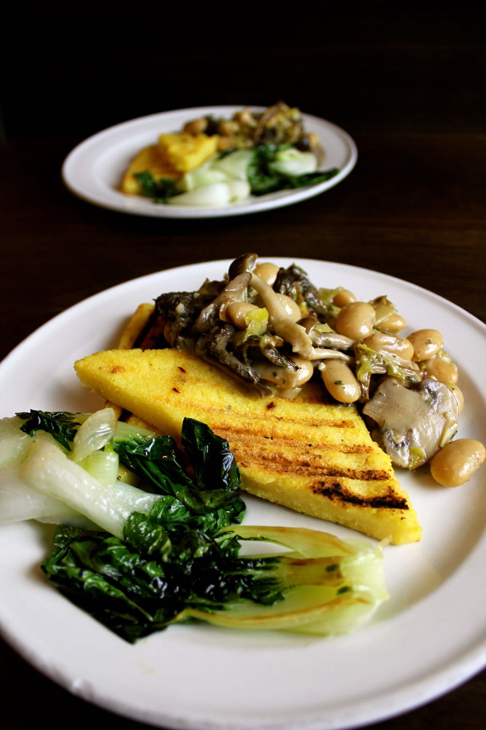 Vegan Creamy Mushrooms and polenta, served on a white plate.