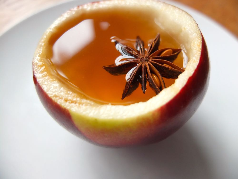 Using a hollow apple on a plate as a cup for spiced apple juice.