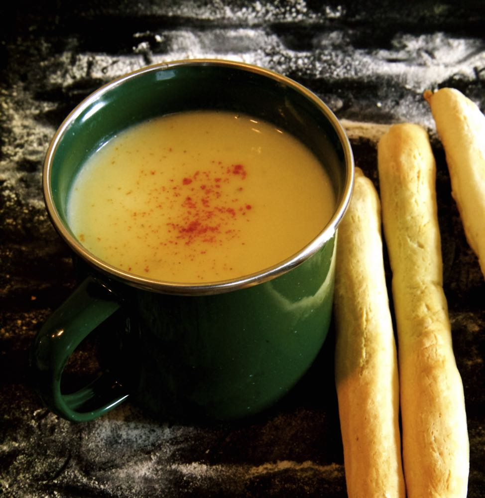 Cauliflower cheese soup in a metal cup, served with homemade breadsticks.