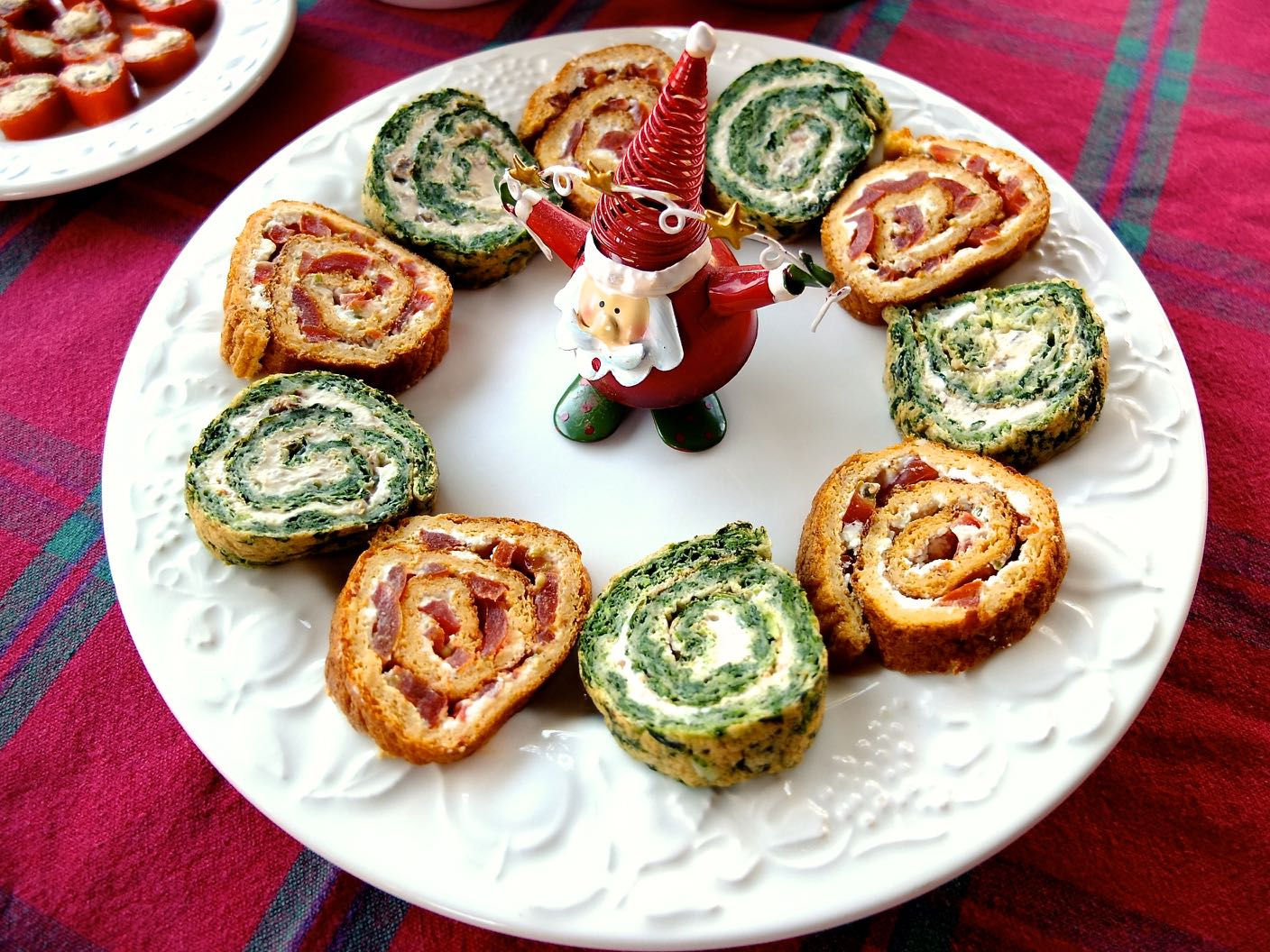 Christmas Roulades on a plate surrounding a small father christmas .