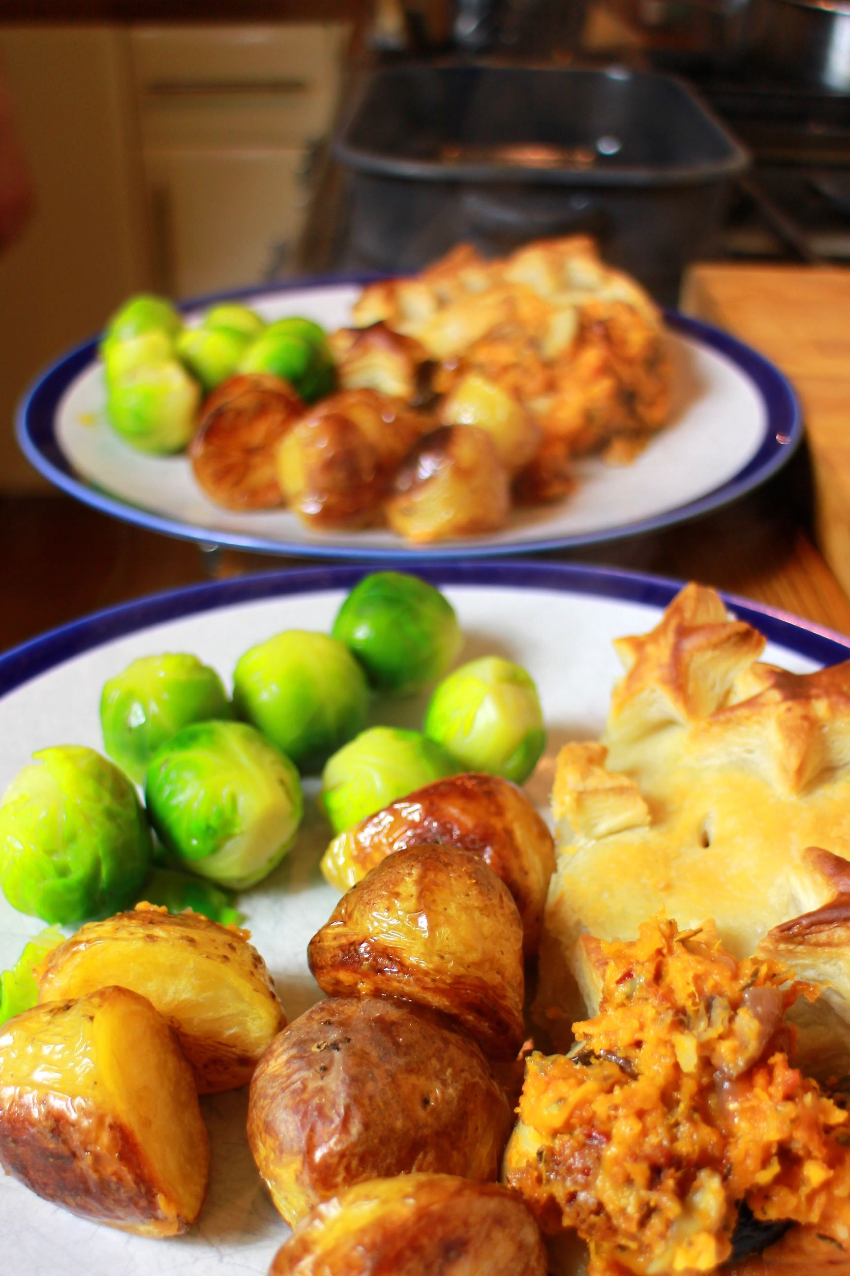 Vegetarian christmas dinner with pie, roast potatoes and boiled sprouts.