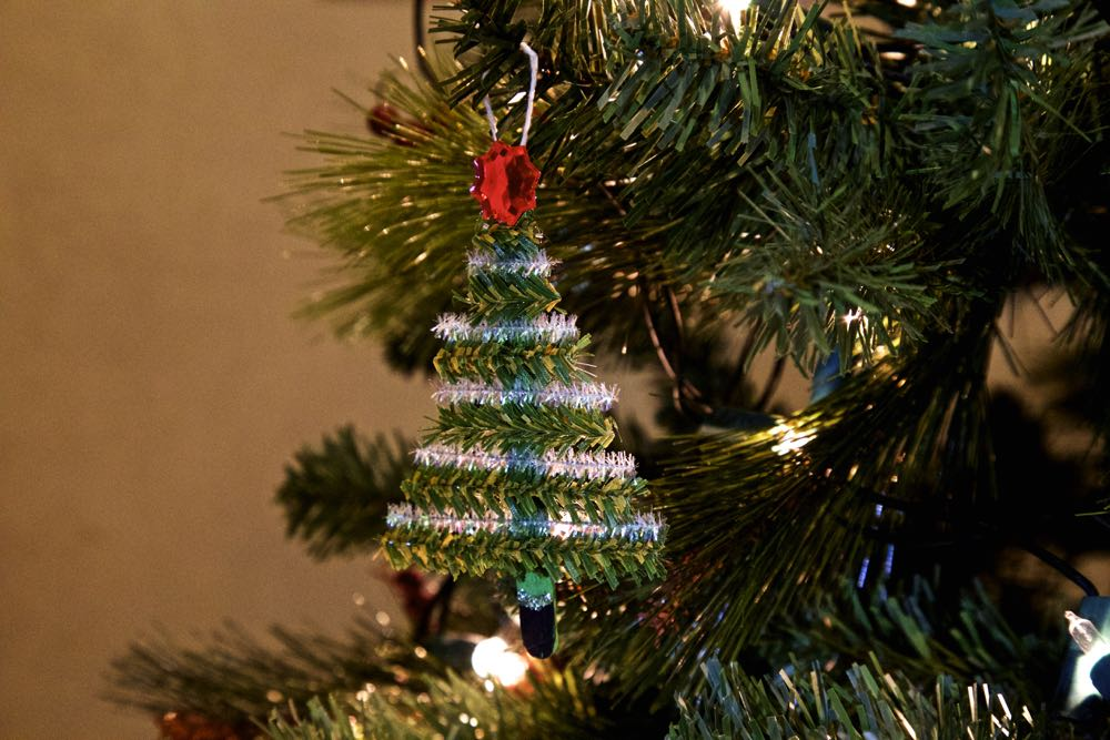 Pipe cleaner christmas tree decoration, hanging from a branch.
