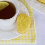 Lemon shortbread served on the saucer of a cup of earl grey tea.