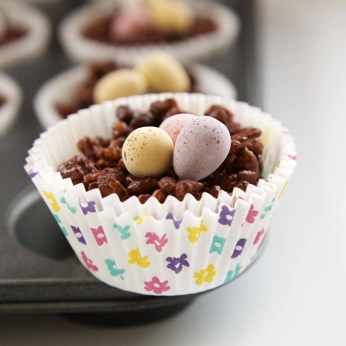 Chocolate Rice Krispie Cake in a pretty spring muffin case topped with chocolate mini eggs.