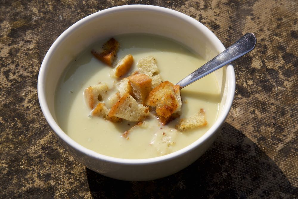 Celery soup with crutons outside on a patio.