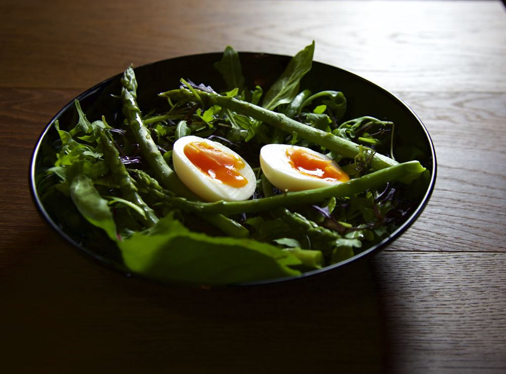 Spring Asparagus Salad with Eggs in a black bowl.