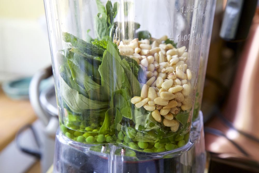 Ingredients for pea and mint pesto in a blender.
