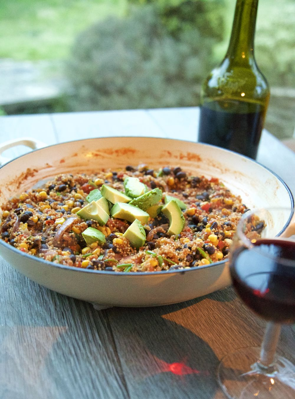 Quinoa chilli ready to eat, with added avocado and served with wine.