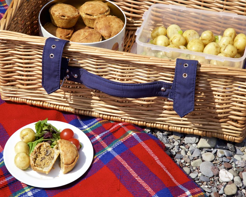 Vegan Hand Raised Picnic Pies with a picnic basket on a rocky beach.