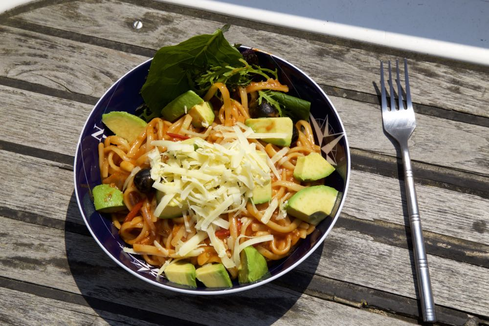 One Pot Pasta Vegetarian Puttanesca with avocado and grated cheese.