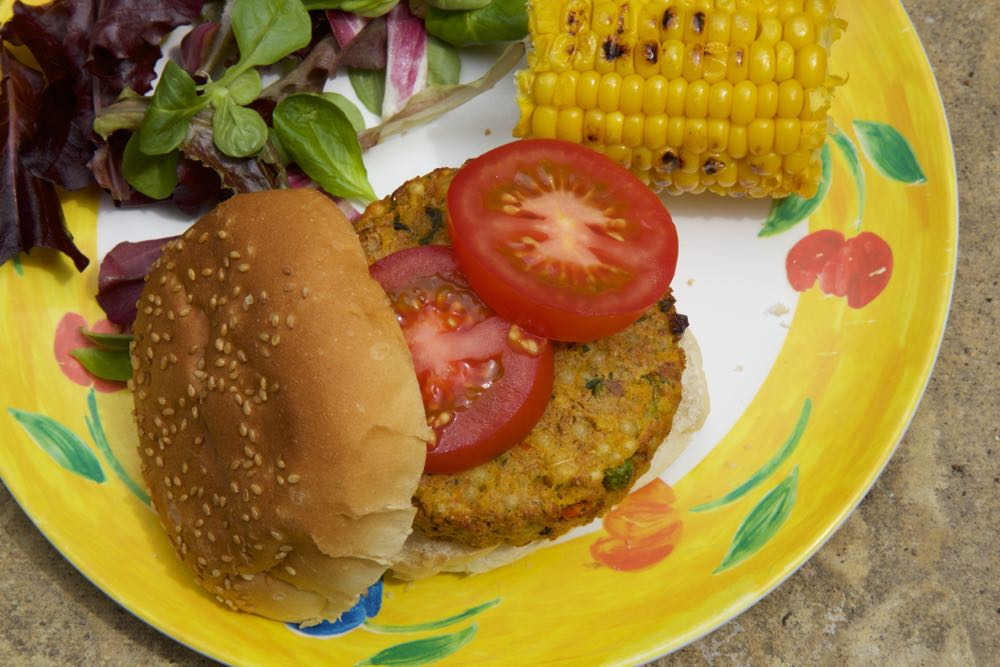 Vegetarian Couscous and Sweet Potato Burgers with tomato and corn on the cob.