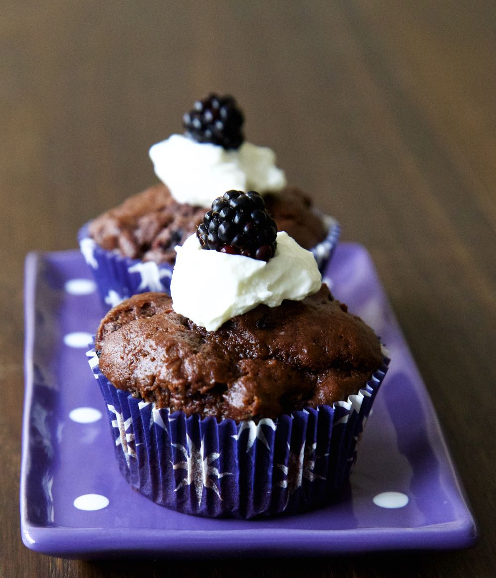 Double Chocolate and Blackberry Muffins, topped with greek yoghurt and a whole blackberry.