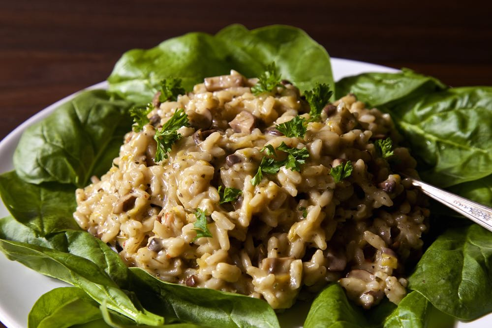 Easy Vegan Mushroom Risotto served on a bed of spinach leaves.