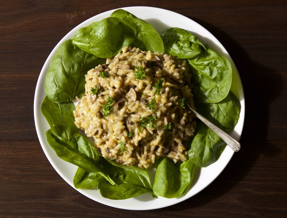 Easy Mushroom Risotto on spinach leaves, topped with parsley.