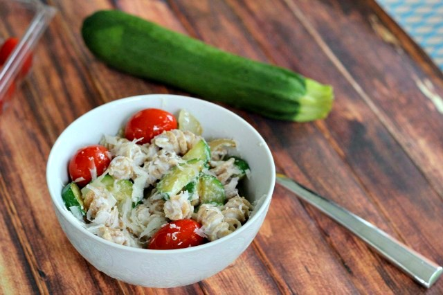 Ricotta and Zucchini Pasta in a small bowl, served with whole cherry tomatoes.