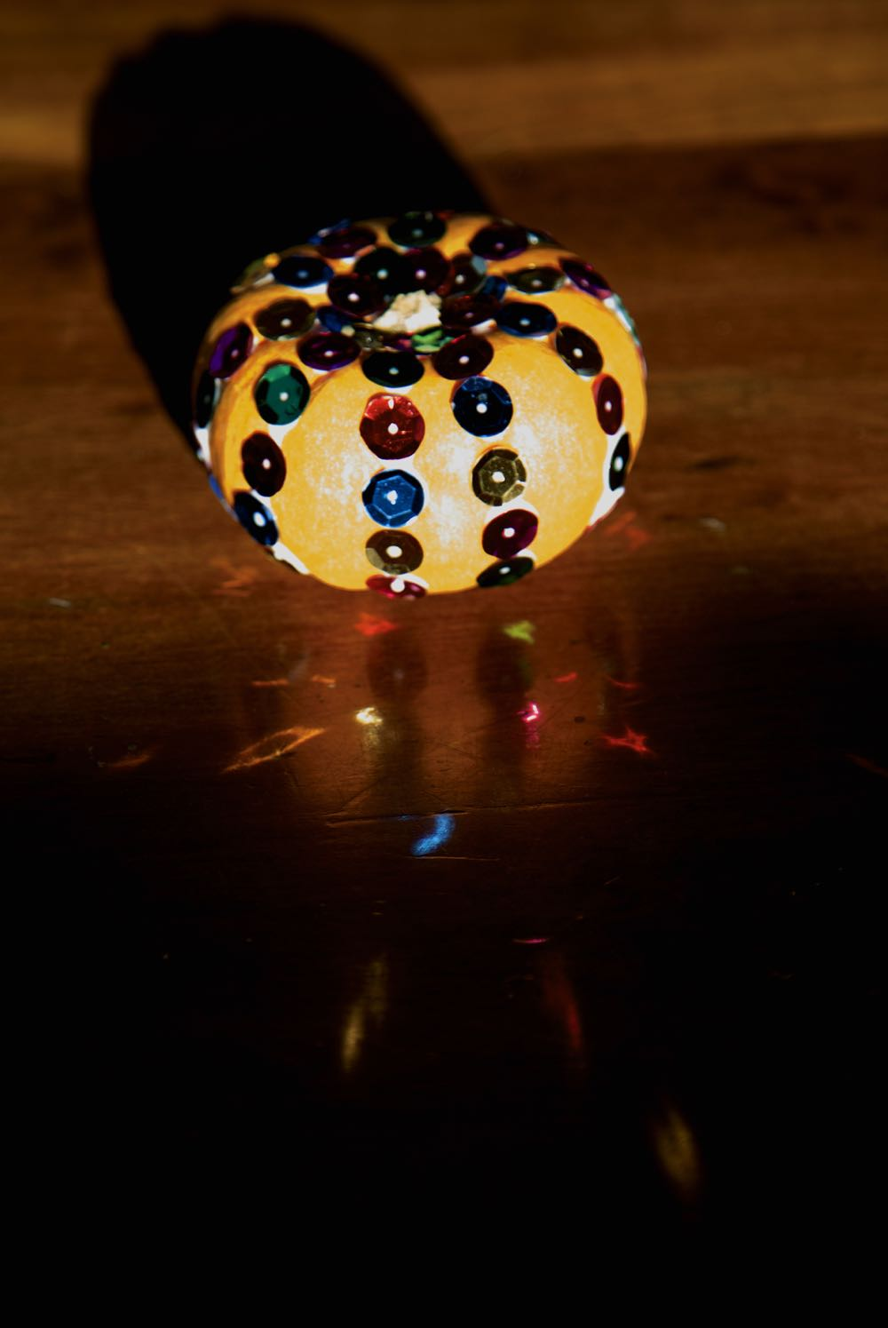 Light reflecting off the sequins onto the table.