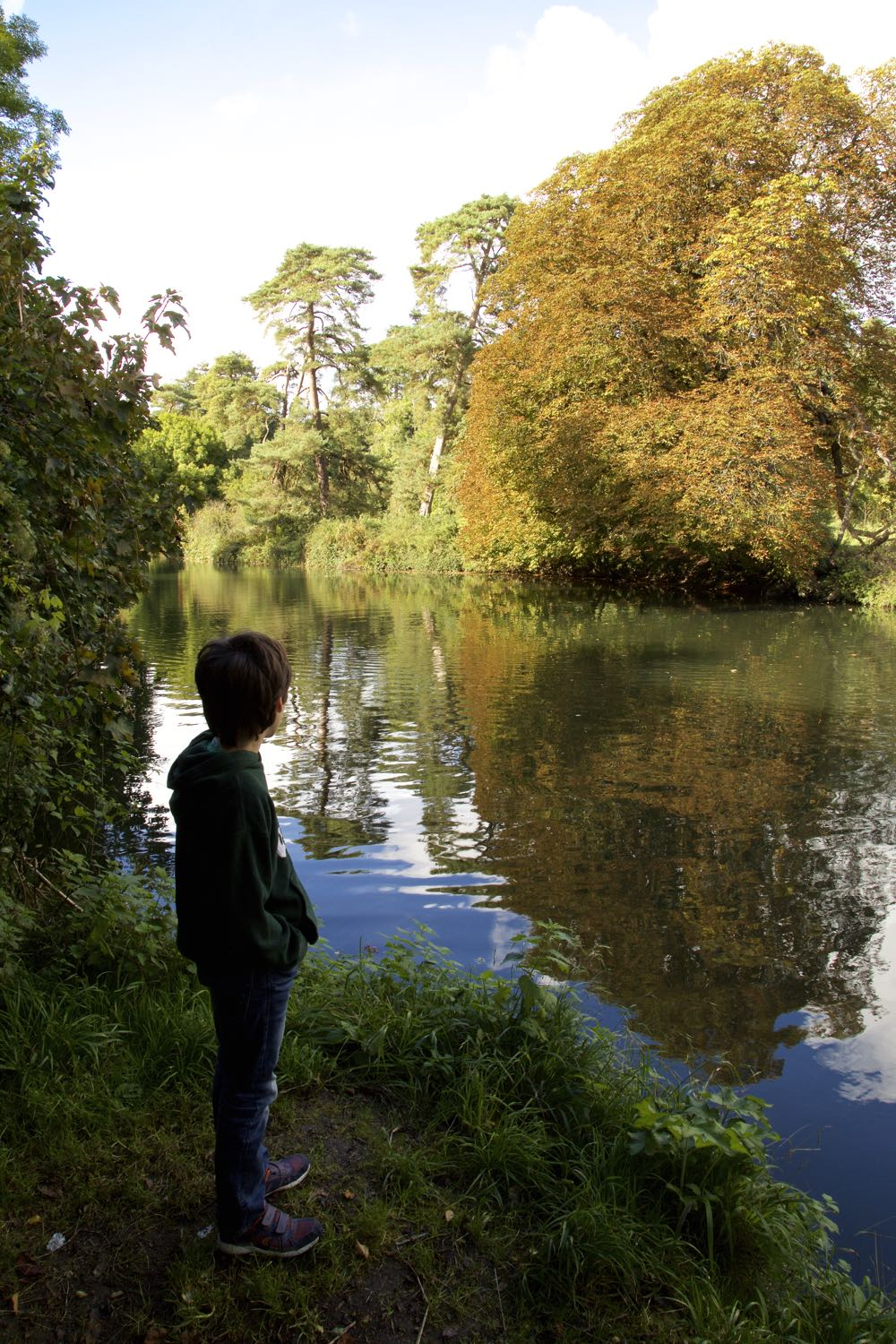 Young boy on an autumn walk by the river.