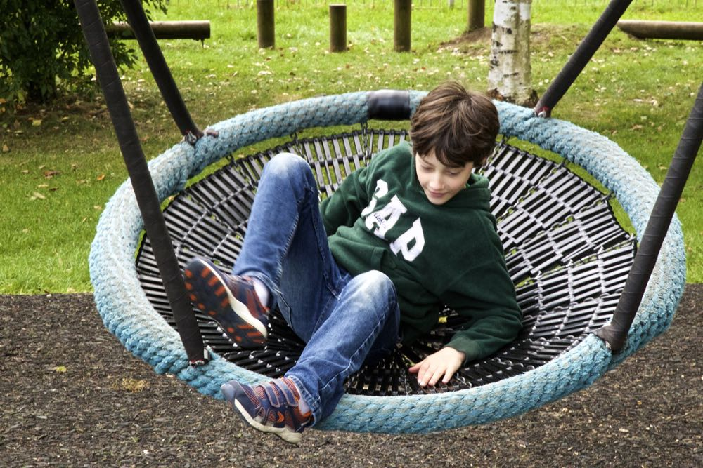 Young boy playing on a large swing.