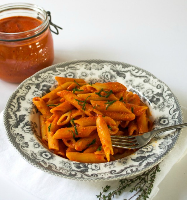 Arrabbiata sauce and penne on a patterned plate, alongside a kilner jar filled with sauce.