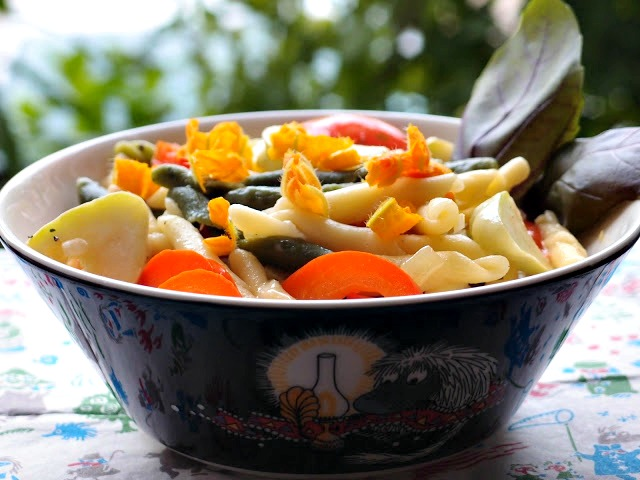 Vegetables and Pasta with courgette flowers in an illustrated bowl.