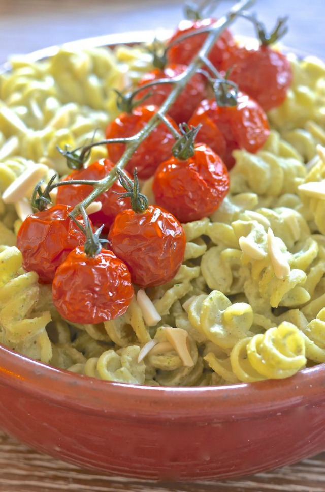 Creamy Vegan Pasta Salad topped with a stem of roasted tomatoes.