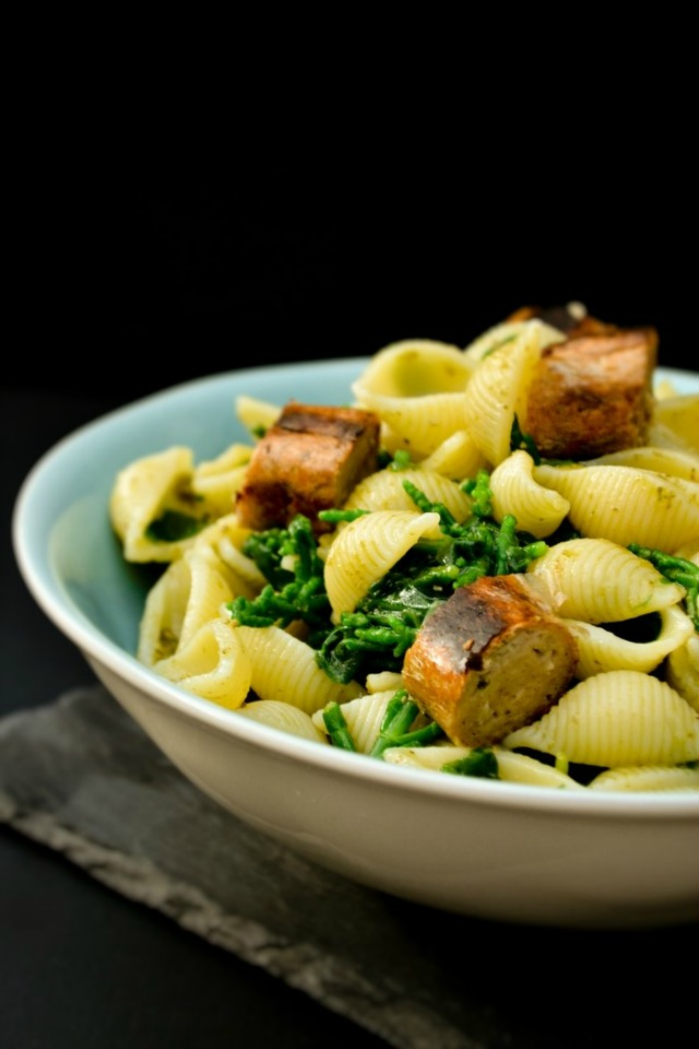 Pasta with Sausages and Samphire on a dark background.