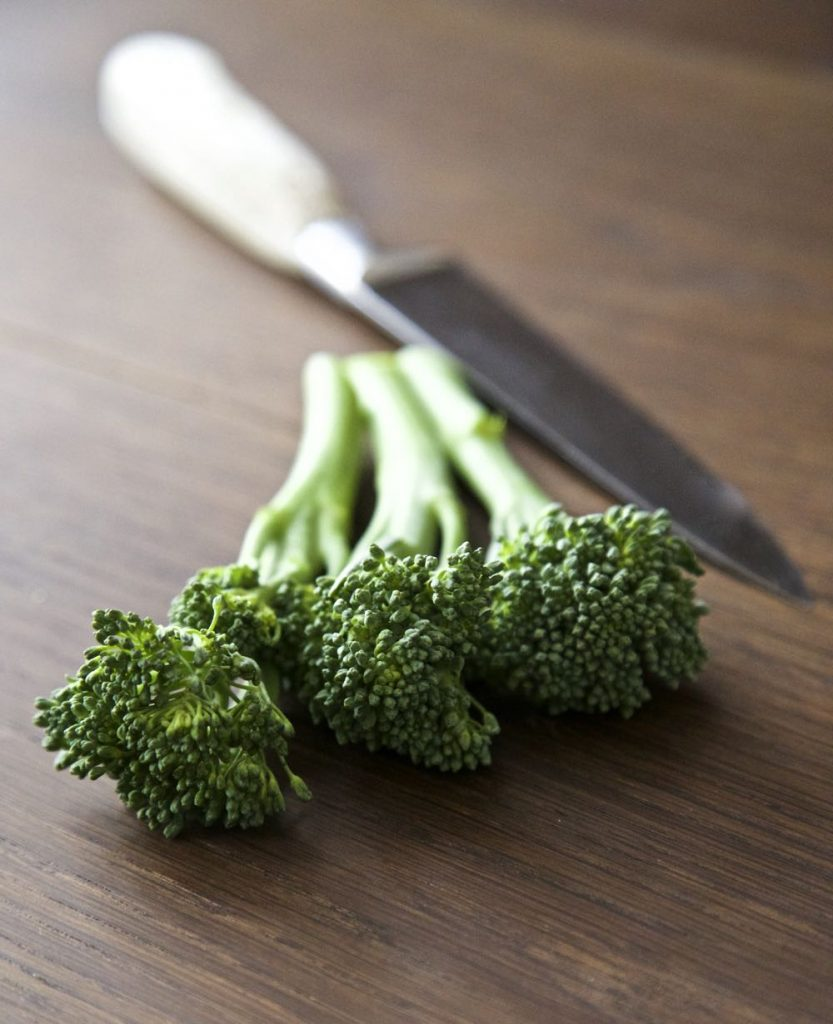 Raw Tenderstem Broccoli with a knife in the background.