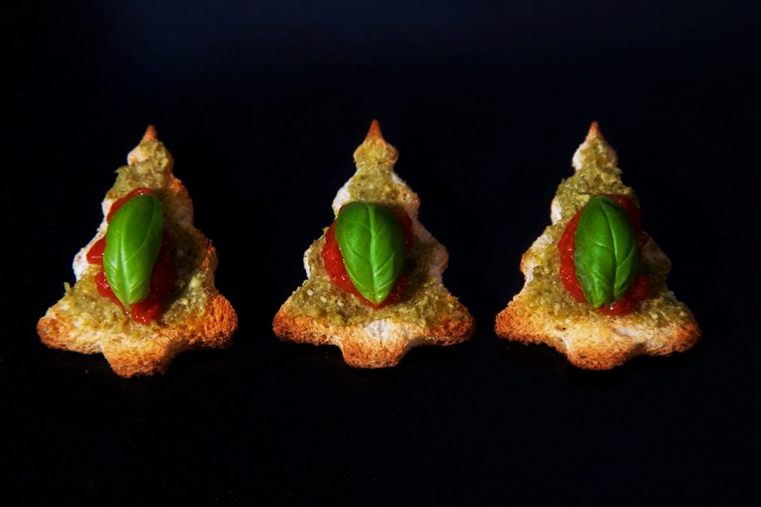 Vegan Canapés-  Recipe for Pesto and Tomato Christmas Tree Bruschetta! You see them here lined up as a three looking lovely and festive topped with a splurge of tomato puree and a basil leaf.