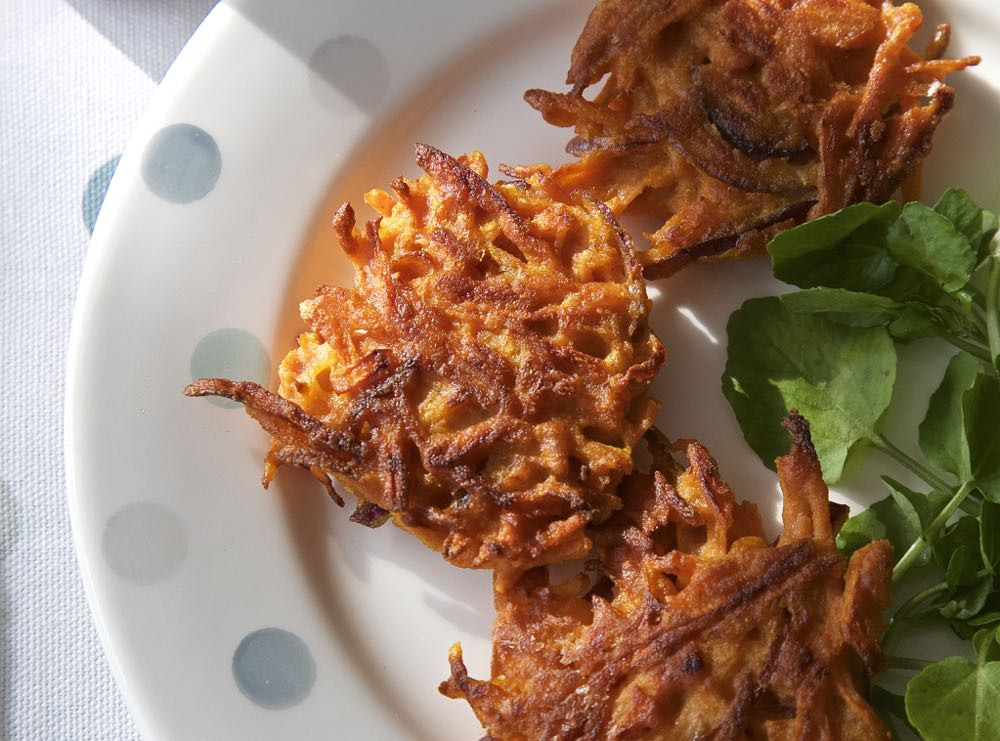 Vegan Carrot Fritters with spinach leaves.