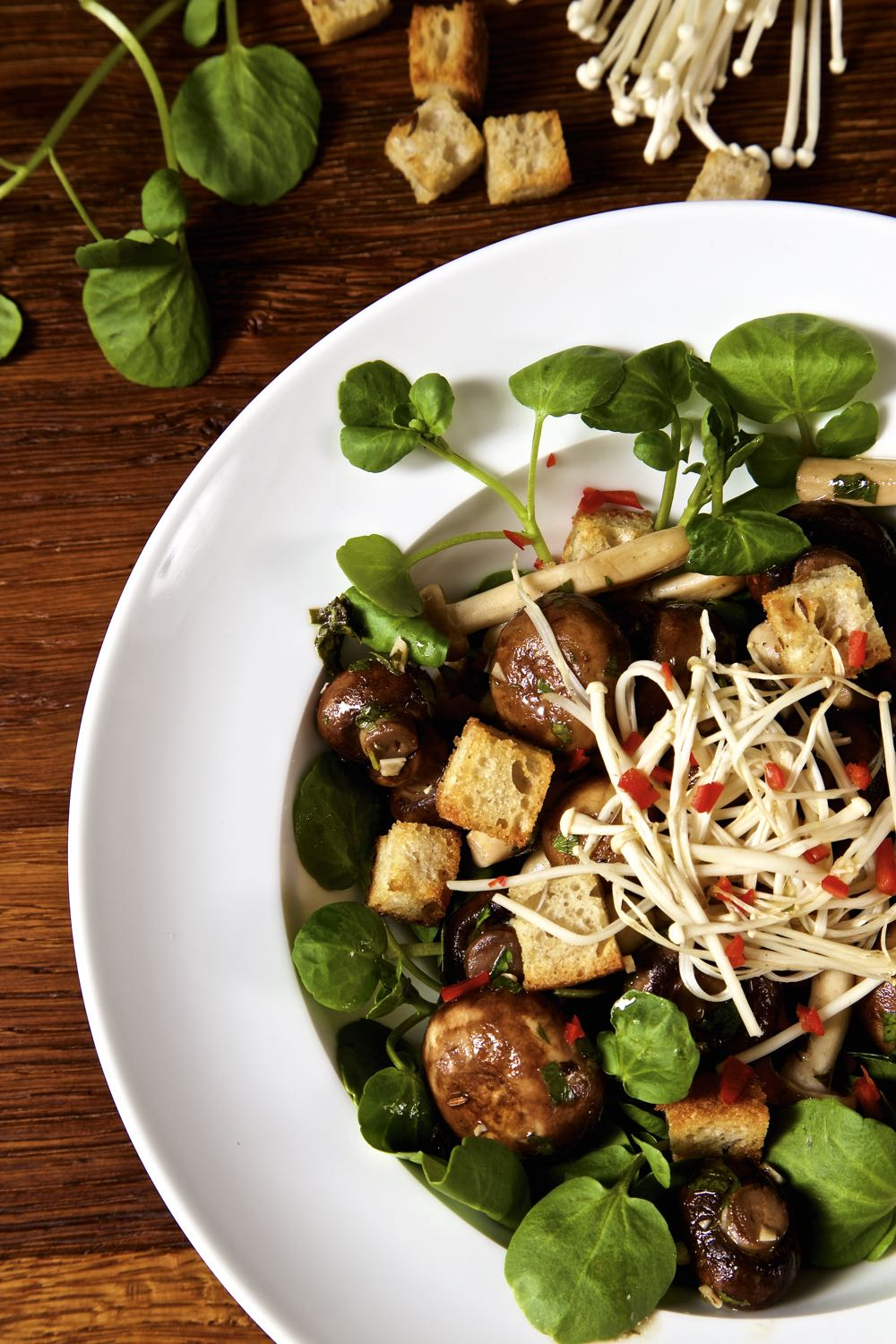 Marinated Mushrooms with cumin croutons and watercress in a white bowl.