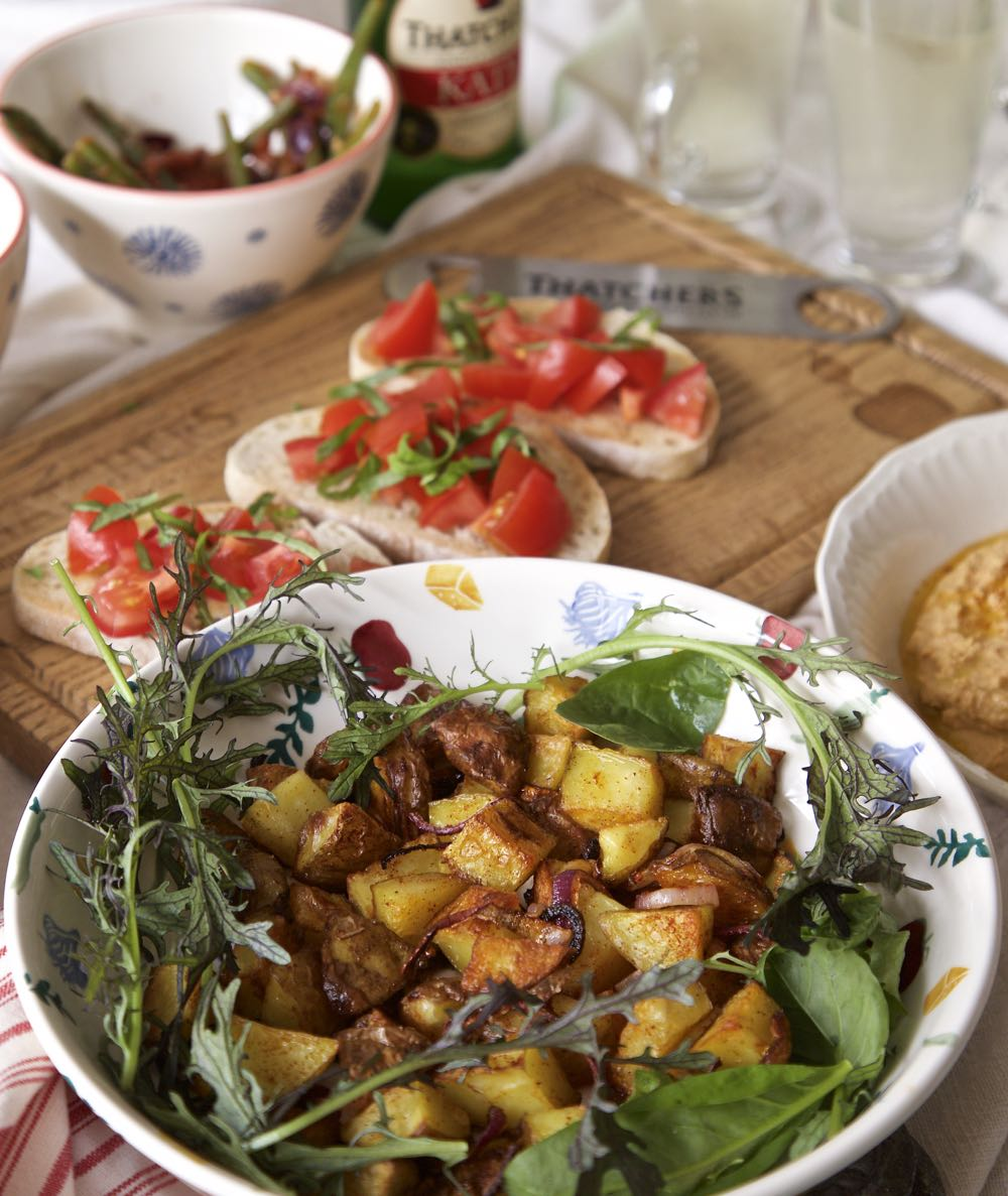 Paprika Potatoes with salad alongside sourdough with fresh tomato.