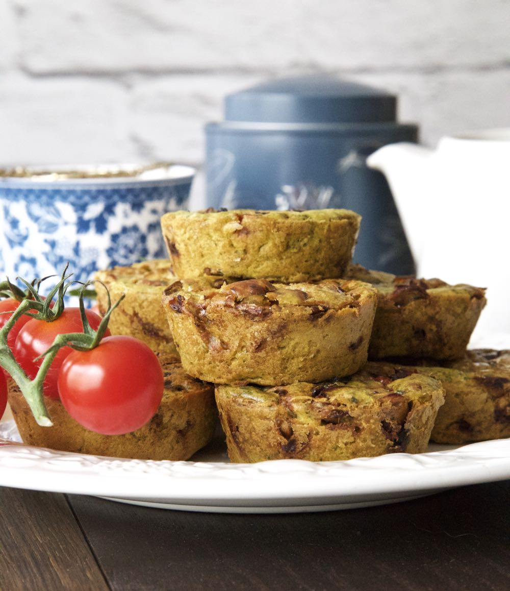 A pyramid of vegan breakfast muffins with tea and tomatoes.