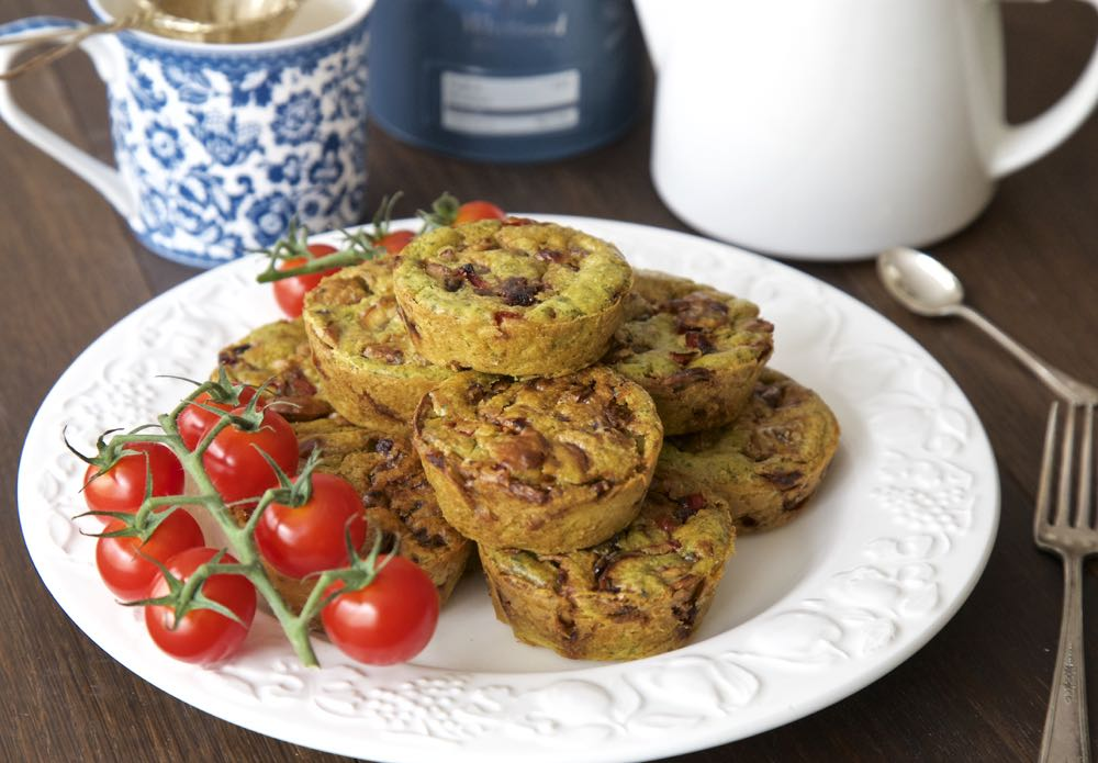 Vegan Full English Breakfast Muffins with cherry tomatoes and a cup of tea.