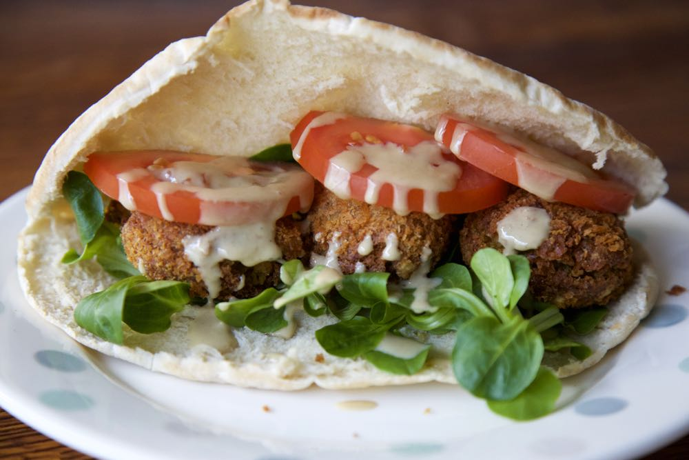 Easy Vegan Chickpea Falafels in soft pitta pockets with crisp salad leaves, juicy tomatoes and a tahini drizzle.
