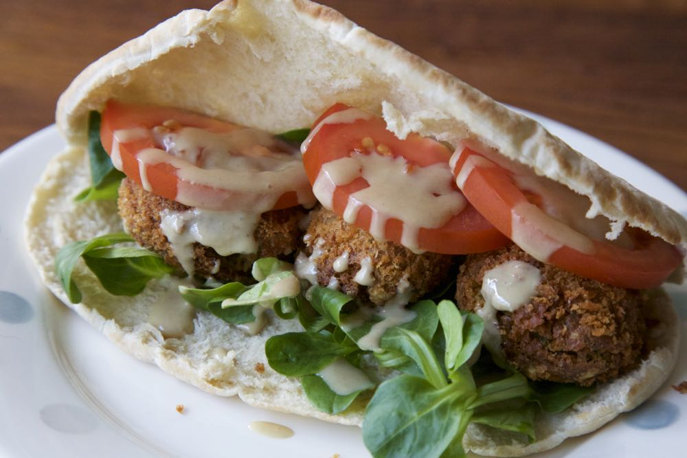 Chickpea falafel served in soft white pitta bread with salad leaves, tomato and tahini.