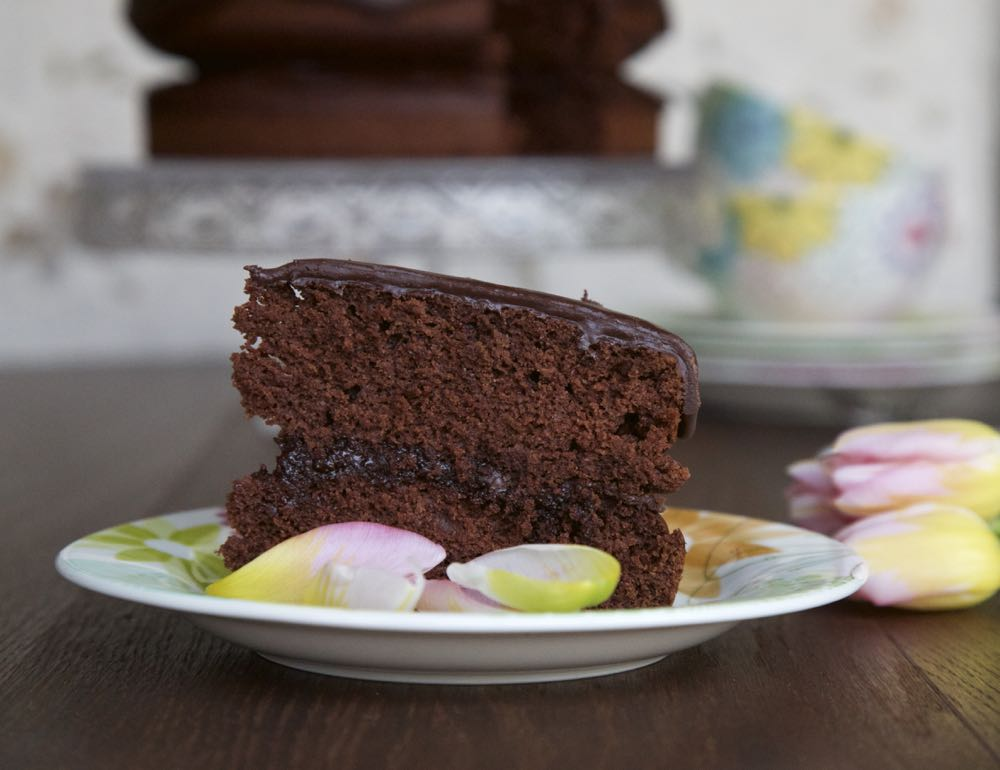The ultimate vegan chocolate fudge cake surrounded by tulip petals.
